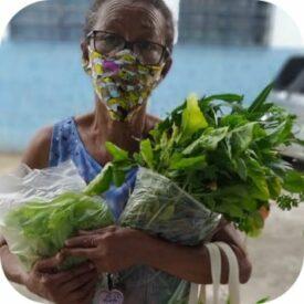 Senhora recebe doação de alimentos orgânicos.